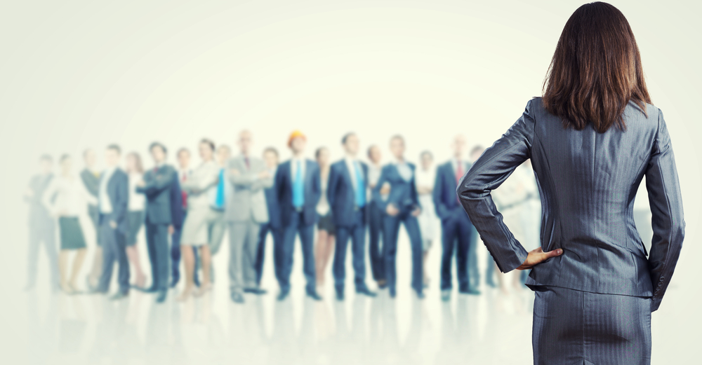 Powerful businesswoman standing with back with business team at background-1