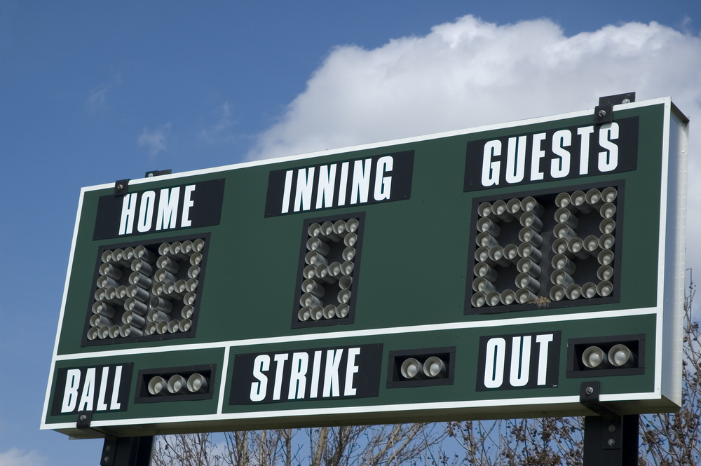 Scoreboard above softball field on a spring day, blue sky and cumulus cloud in background