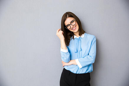 Smiling businesswoman in glasses standing over gray background. Wearing in blue shirt and glasses. Looking at camera
