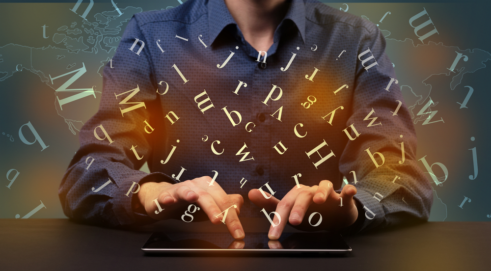 Young man in suit and formal clothing typing with letters around