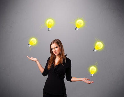 beautiful young lady standing and juggling with light bulbs