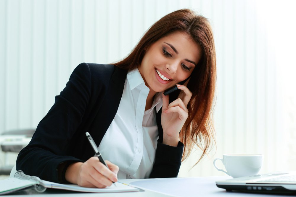 Young happy businesswoman talking on the phone and writing notes in office-2
